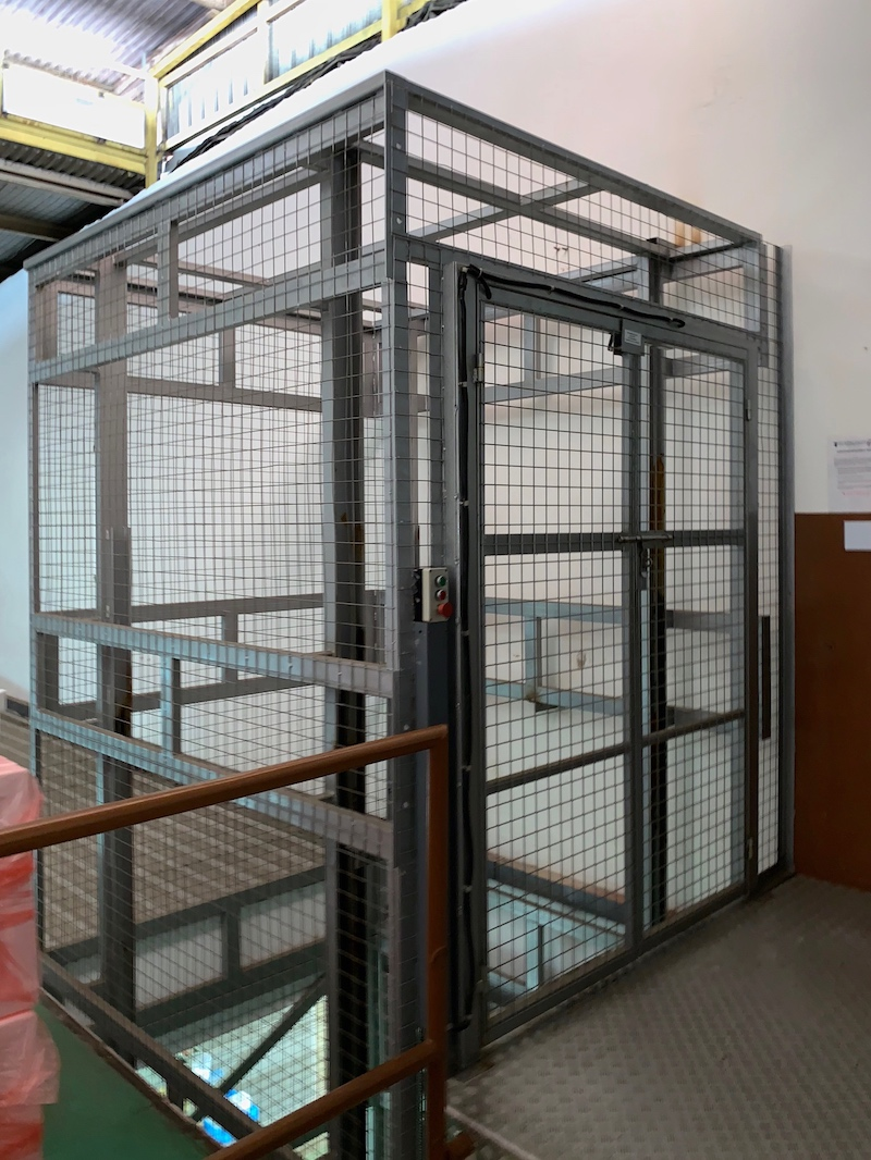 Wire-mesh enclosure in painted steel finishing, cargo platform lift
